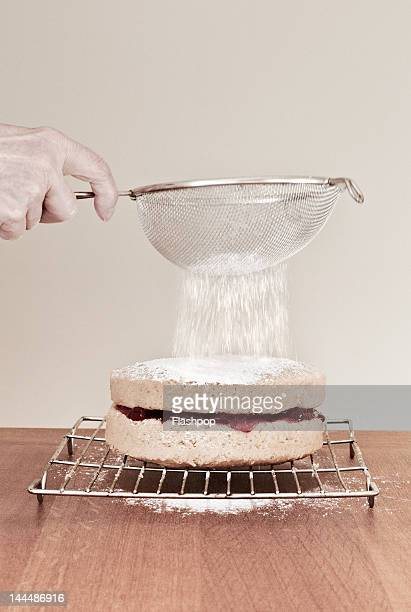 Woman sieving icing sugar on top of a cake