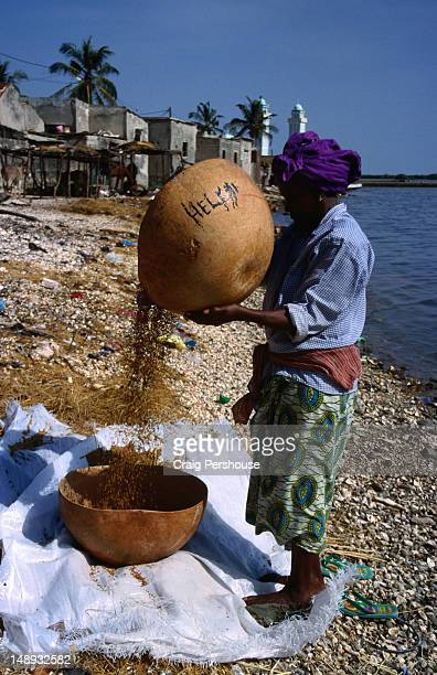 Woman sifting grain on beach, Joal-Fadiouth.