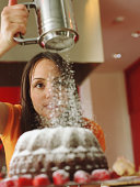 Woman sifting powdered suger over bundt cake