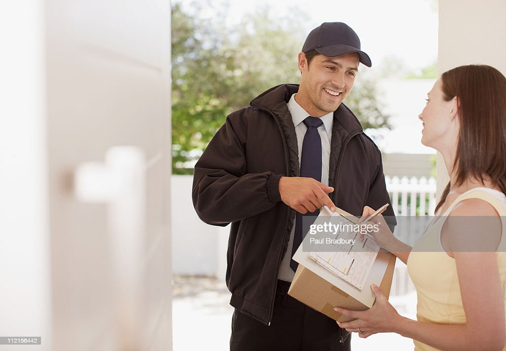 Woman signing box receipt for delivery man : Stock Photo