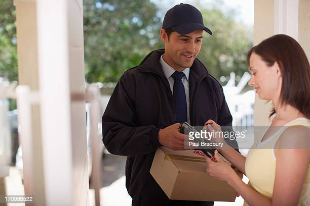 Woman signing for box from delivery man