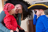 Woman signing 'Pirate' to communicate with her sons dressed as pirates at Halloween