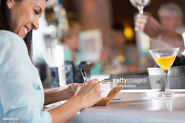 Woman signing receipt after paying bar tab in restaurant