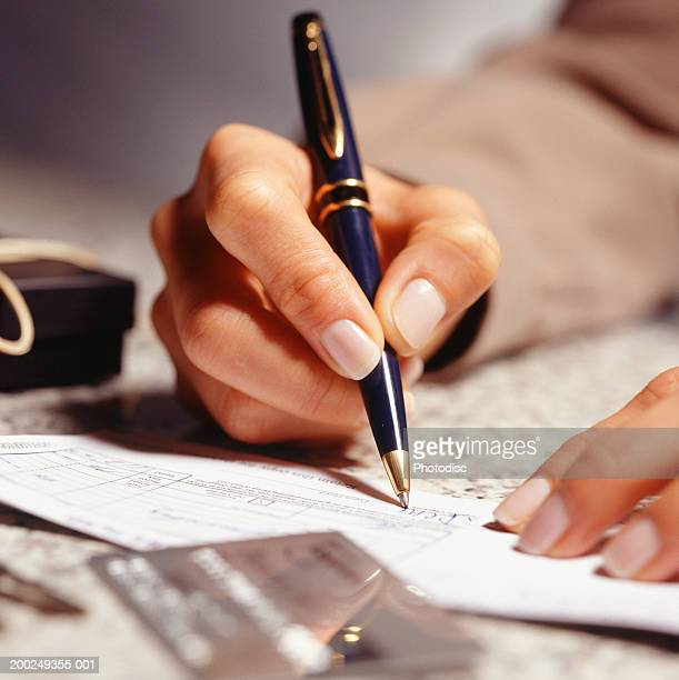 Woman signing receipt in office, (Close-up)