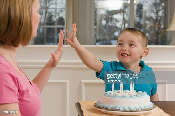 Woman signing the number '5' in American sign language while communicating with her son