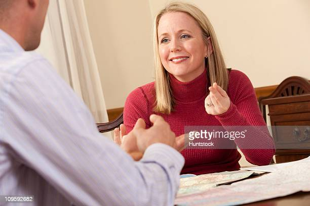 Woman signing the phrase 'What are you doing' in American Sign Language while communicating with a man