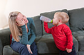Woman signing the word 'Bed' in American Sign Language while her son is drinking milk