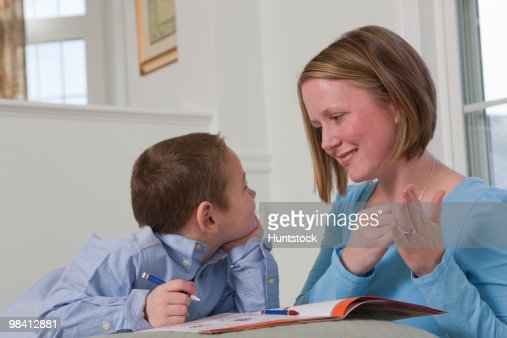 Woman signing the word 'Draw' in American Sign Language while teaching her son : Foto de stock