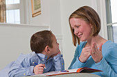 Woman signing the word 'Draw' in American Sign Language while teaching her son