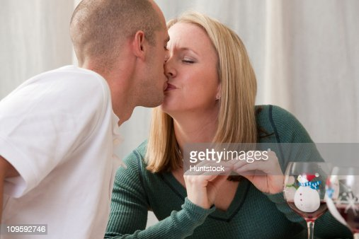 Woman signing the word 'Kiss' in American Sign Language while kissing her husband : Stock Photo