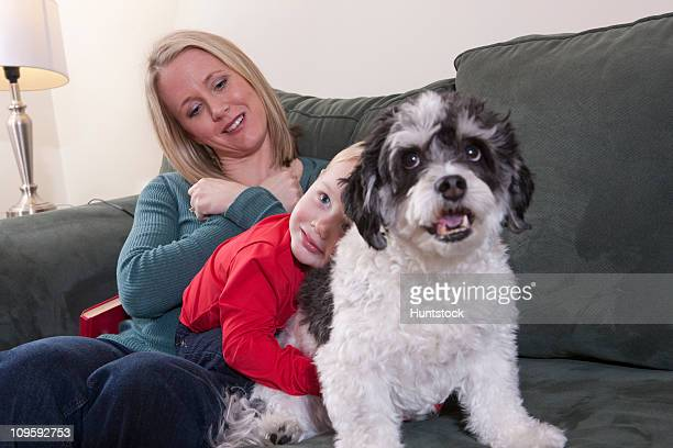 Woman signing the word 'Love' in American Sign Language while her is son hugging a dog