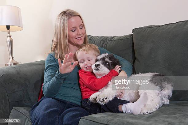Woman signing the word 'Puppy' in American Sign Language while her son is hugging a dog