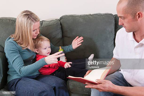 Woman signing the word 'Read' in American Sign Language while teaching her son