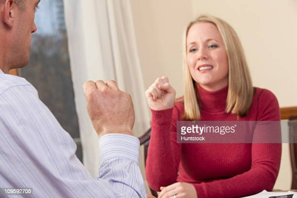 Woman signing the word 'Yes' in American Sign Language while communicating with a man