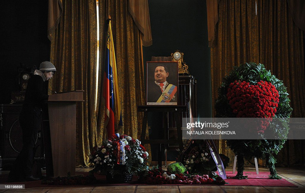 A woman signs a condolence book near a portrait of late Venezuelan President Hugo Chavez at the Venezuela's embassy in Moscow on March 6, 2013. Russian President Vladimir Putin hailed today his late Venezuelan counterpart Hugo Chavez as an uncommon and strong man who had made a huge contribution to relations between Moscow and Caracas. Russia enjoys close military ties with Venezuela, which also represents one of the main oversees investment targets of the giant state oil company Rosneft.