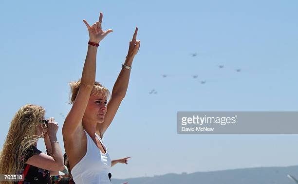 A woman signs a one and a three with her fingers to helicopters some of which are seen behind her flying in with members of the 13th MEU US Marines...
