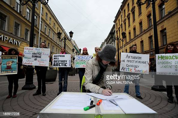 A woman signs a petition as others hold posters during a protest in support of the 'Arctic 30' detained Greenpeace activists in central Saint...