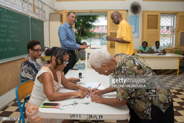 A woman signs after casting her ballot during the secound round of the French legislative elections at a polling station in PointeaPitre on June 17...