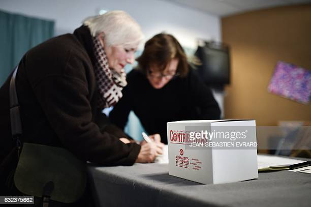 A woman signs in at a polling station next to a donation box during the first round of the leftwing primary for the 2017 French presidential election...