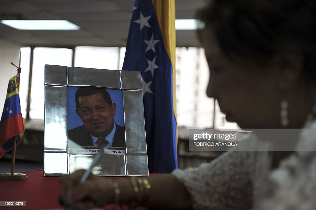A woman signs the book of condolences for the death of Venezuelan President Hugo Chavez at the Venezuelan embassy in Panama on March 6, 2013. Condolences poured in Wednesday from world leaders who had found common cause with Venezuela's Hugo Chavez in his 14-year campaign to galvanize the Latin American left and defy US 'imperialism.' AFP PHOTO/ Rodrigo ARANGUA