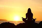 Back view of a full body of woman silhouette sitting doing yoga lotus pose exercises at sunrise with the sun horizon and ocean in the background