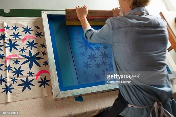 Woman silk-screening fabric