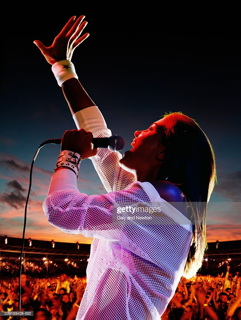 Woman singing, holding microphone, arm raised, crowd in background : Stock Photo
