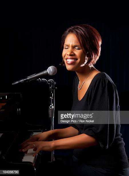A Woman Singing Into A Microphone And Playing The Piano
