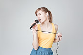 Beautiful young woman singing into a microphone karaoke showing expressions and feelings