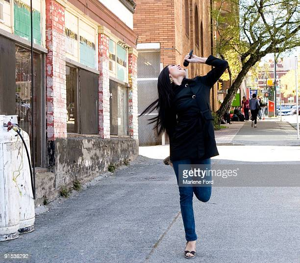 Woman singing into microphone on sidewalk