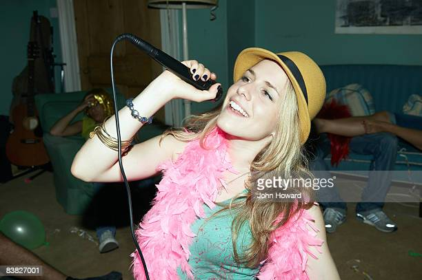Woman singing karaoke at house party