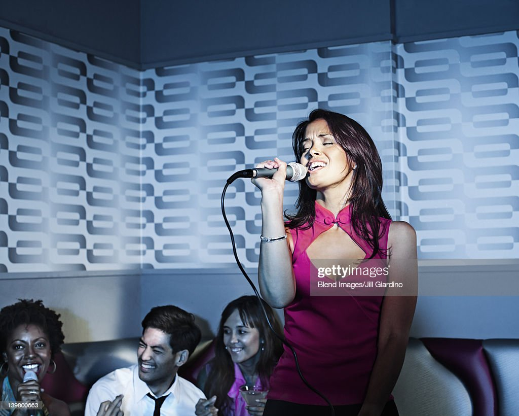 Woman singing karaoke in nightclub : Stock Photo