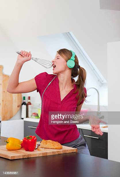 Woman singing with whisk in kitchen