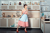 The girl opened her mouth much because when she sings cleans the kitchen. She carried a mop for washing floors.