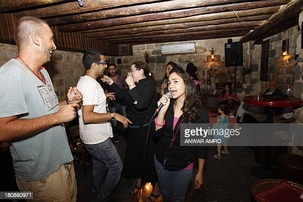 A woman sings as others dance at a karaoke bar in Damascus on September 13 2013 When night falls in Damascus gaggles of determined revellers still...