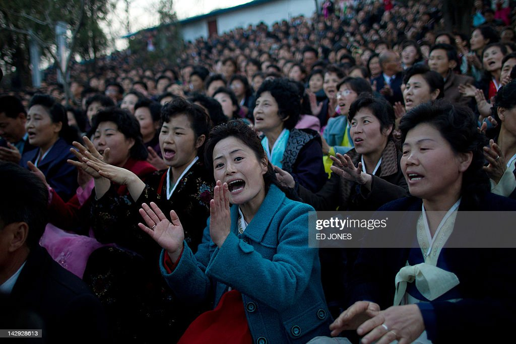 A woman sings as she waits for a fireworks display to mark 100 years since the birth of North Korea's founder Kim Il-Sung in Pyongyang on April 15, 2012. North Korea's new leader Kim Jong-Un delivered his first public speech and vowed to push for 'final victory' for his impoverished state despite a failed rocket launch two days ago, as the country celebrated the 100th anniversary of former leader Kim Il-Sung. AFP PHOTO / Ed Jones