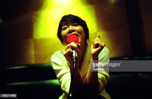 A woman sings her favorite song at a local Karaoke club called Party World Cashbox Shanghai is China's largest and most dynamic city It's modern and...