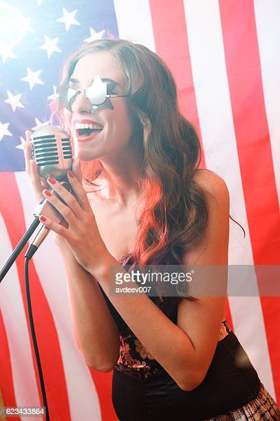 Woman Sings on a Background of the American Flag