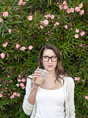 Woman sipping beverage by flowering bush
