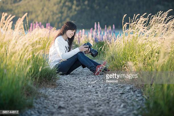 A woman sit and look at picture in camera in the middle of field.