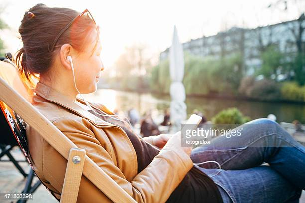 Femme s'asseoir en terrasse de café et écouter de la musique
