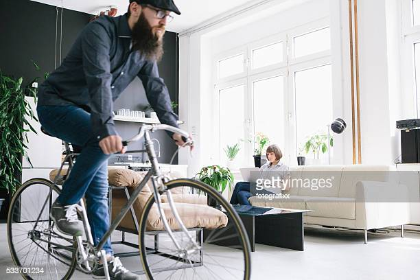 woman sit on couch in a loft, hipster drive bicycle
