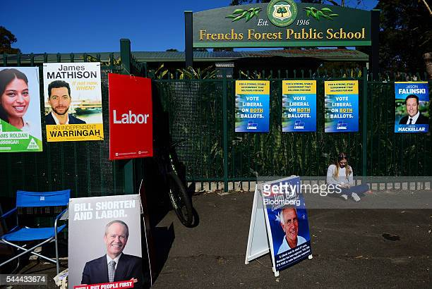 A woman sit using a smartphone near campaign posters of various candidates outside polling station in Sydney Australia on Saturday July 2 2016 Prime...