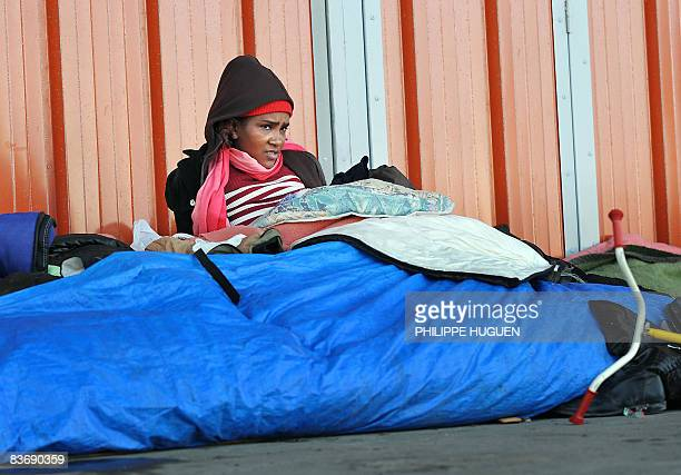 'A CALAIS LES REFUGIES AFGHANS VIVENT DANS LA HANTISE DU CHARTER' A woman sits along with other migrants coming from Afghanistan and Middle East...