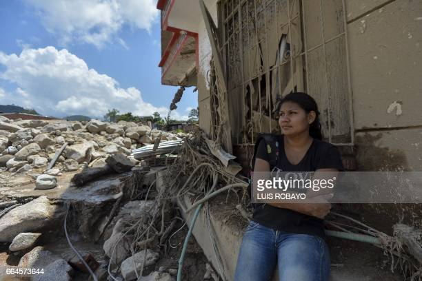 TOPSHOT A woman sits amid the debris left by mudslides caused by heavy rains in Mocoa Putumayo department southern Colombia on April 4 2017 The...