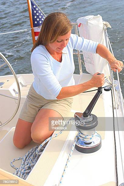 A woman sits and cranks a rope in on a sailboat.