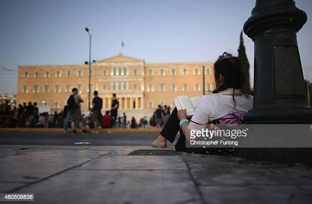 A woman sits and reads a book as antiausterity demonstrators gather in front of the Greek parliament and Eurozone leaders in Brussels continue their...