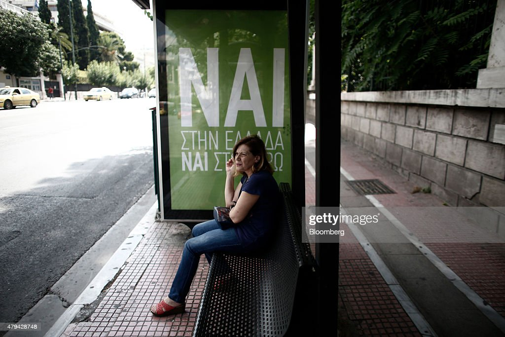 A woman sits and smokes at a bus shelter next to a campaign poster reading 'NAI' or 'Yes' in support of the European Union in Athens Greece on...