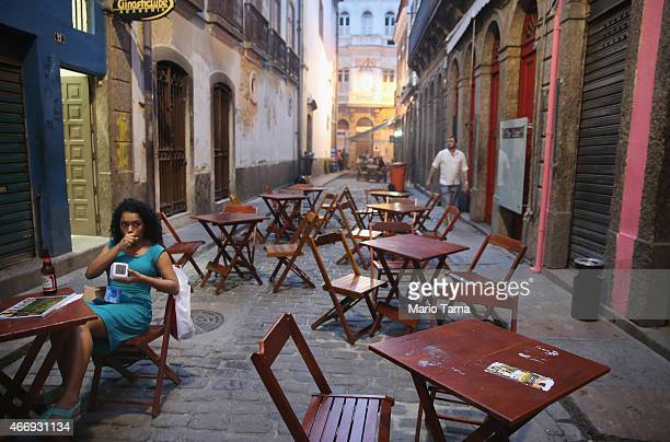 A woman sits as a cafe in Centro on March 19 2015 in Rio de Janeiro Brazil Economic numbers released recently predict rising inflation and...