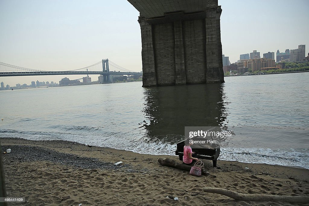 A woman sits at a piano underneath the Brooklyn Bridge on June 3, 2014 in New York City. A grand piano that has mysteriously landed on a sliver of beach under the iconic bridge last week has become an impromptu tourist attraction. While the Mason & Hamlin piano is badly damaged, dozens of people climb onto the beach daily to test out the keys.